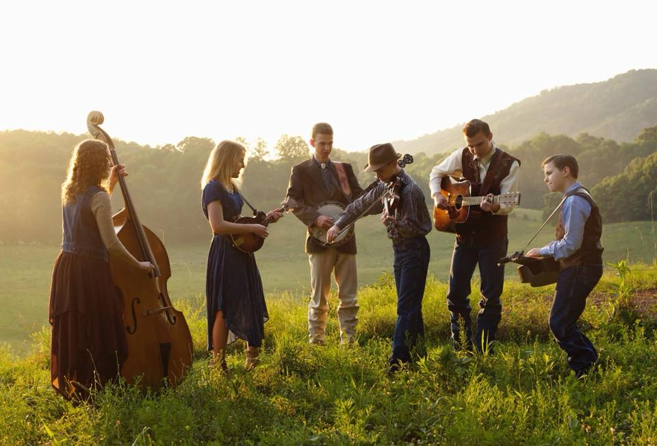 The Family Sowell playing their various instruments: base, mandolin, banjo, fiddle, guitar and dobro, on a pastoral hillside under a hazy sun.